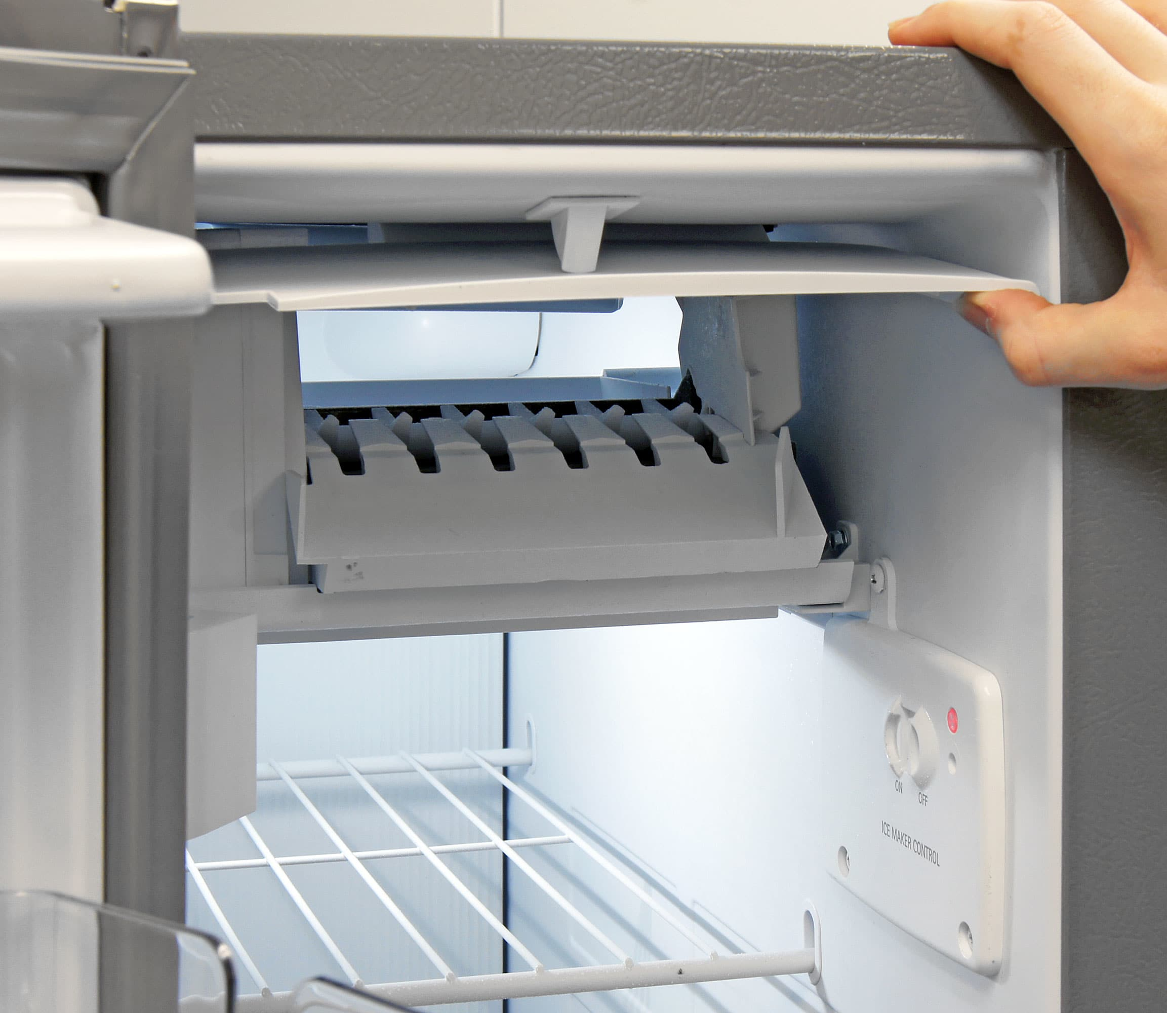 The machine that actually makes the ice is found at the top of the KitchenAid KSF22C4CYY's freezer compartment. The flashing red dot on the side is the dispenser's on/off switch.
