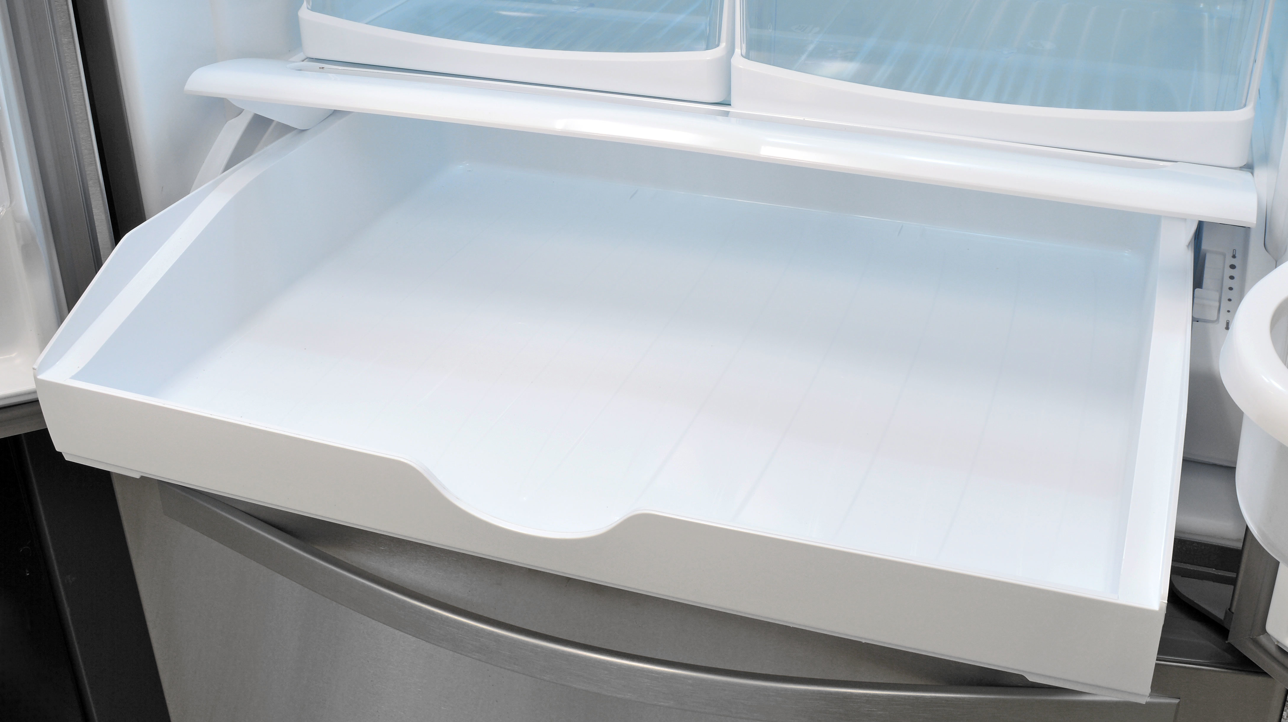 The Whirlpool WRF535SMBM's pantry drawer has an adjustable temperature slide which is hidden when the drawer is shut. You can see it here off on the right side.