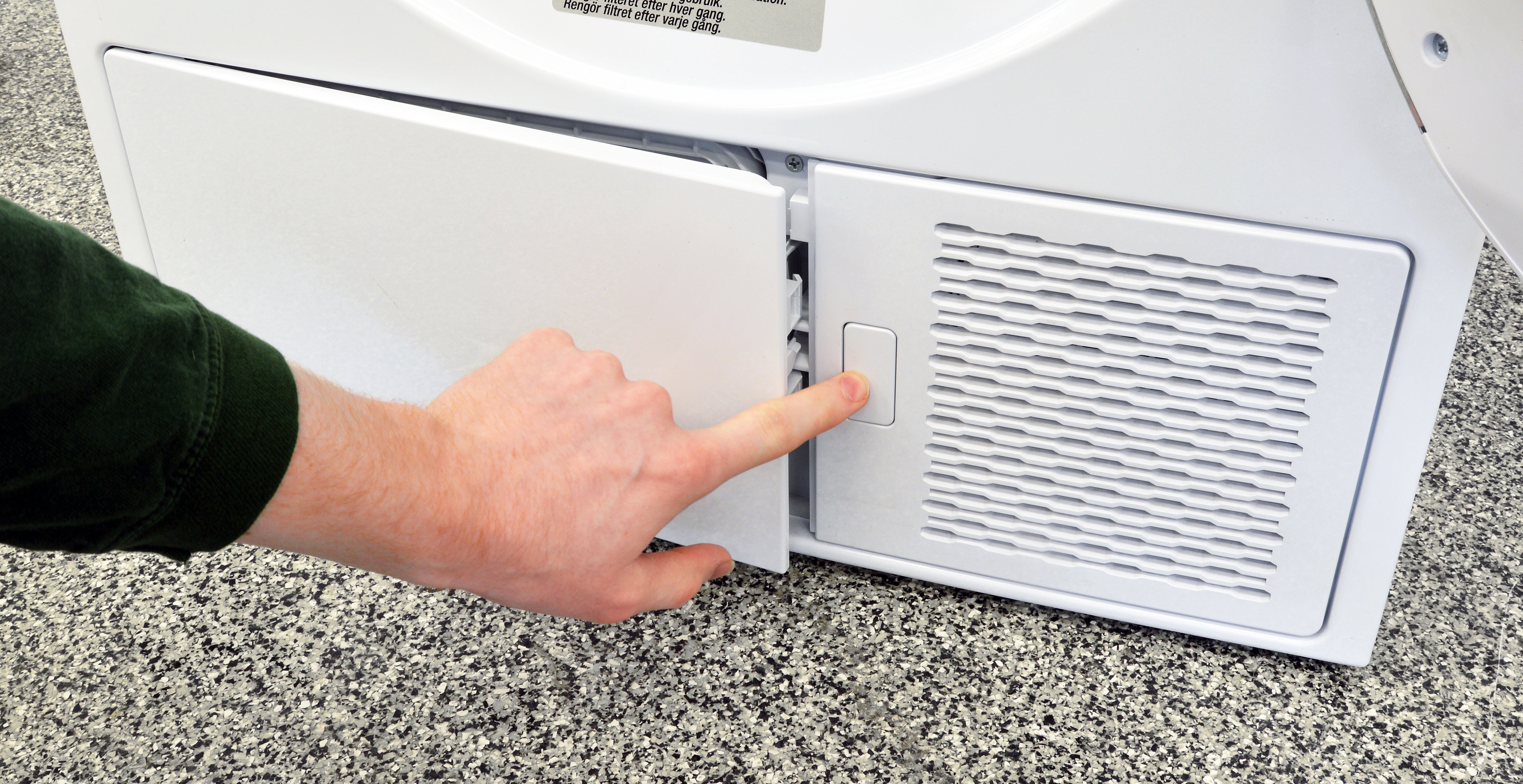 """The small white button under the Blomberg DHP24412W's door pops open a """"hidden"""" compartment that houses the secondary lint trap."""
